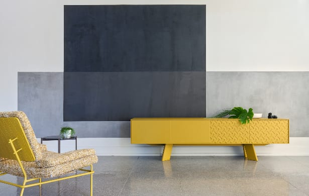 long yellow table and matching chair in front of patterned wall